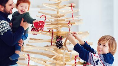 Weihnachtsbaum aus Holz - die Familie schmückt ihn - Foto: iStock/olesiabilkei