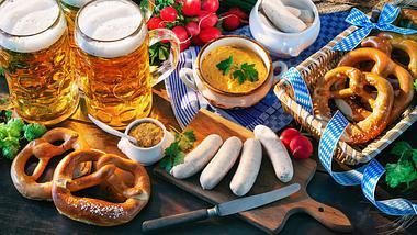 Oktoberfest-Spezialitäten auf einem Holztisch: Bier, Brezeln, Weißwurst, Obatzda - Foto: alexraths / iStock