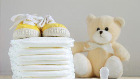 Ein Stapel Windeln neben einem Plüschteddy, gelben Babyschuhen und einem Babyschnuller - Foto: iStock/JuanCi